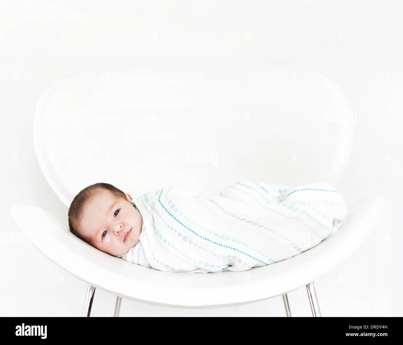 Swaddled baby on white chair - Stock Image