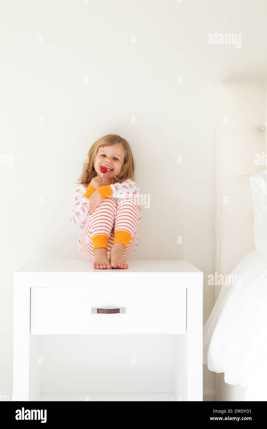 Girl in pajamas sitting on nightstand - Stock Image