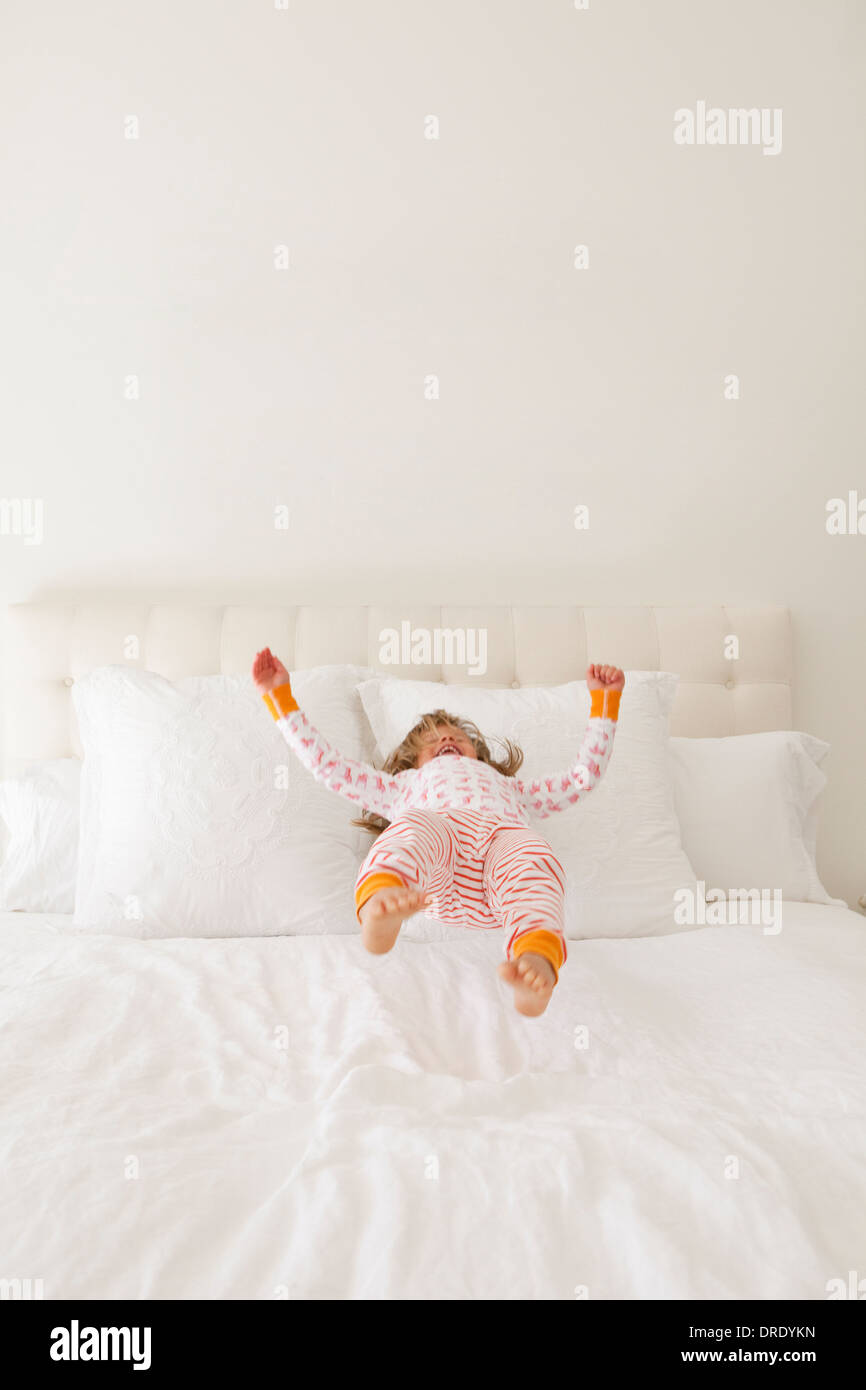 Girl in colorful jammies jumping on bed - Stock Image