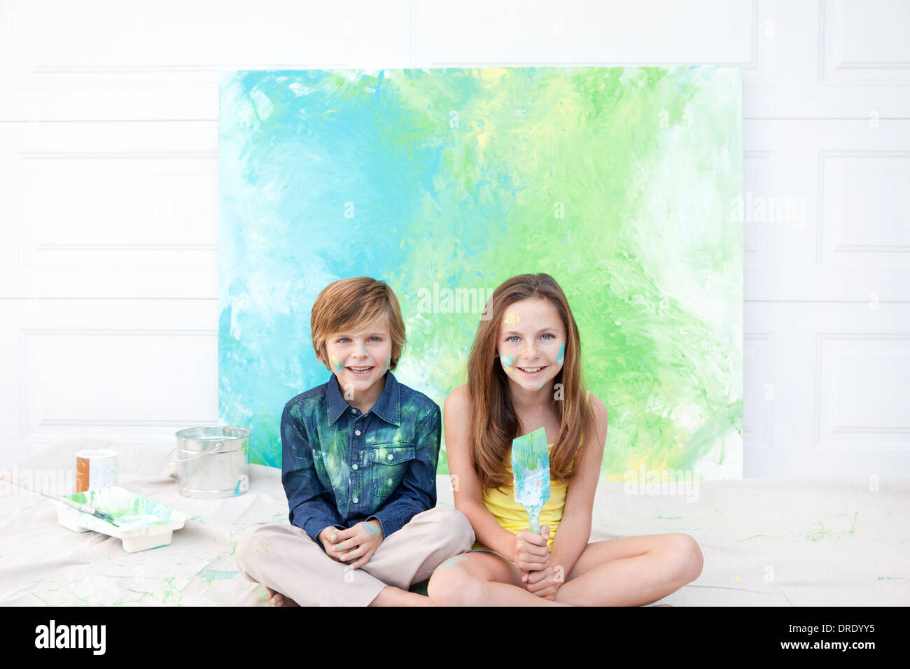 Brother and sister sitting in front of colorful painting - Stock Image