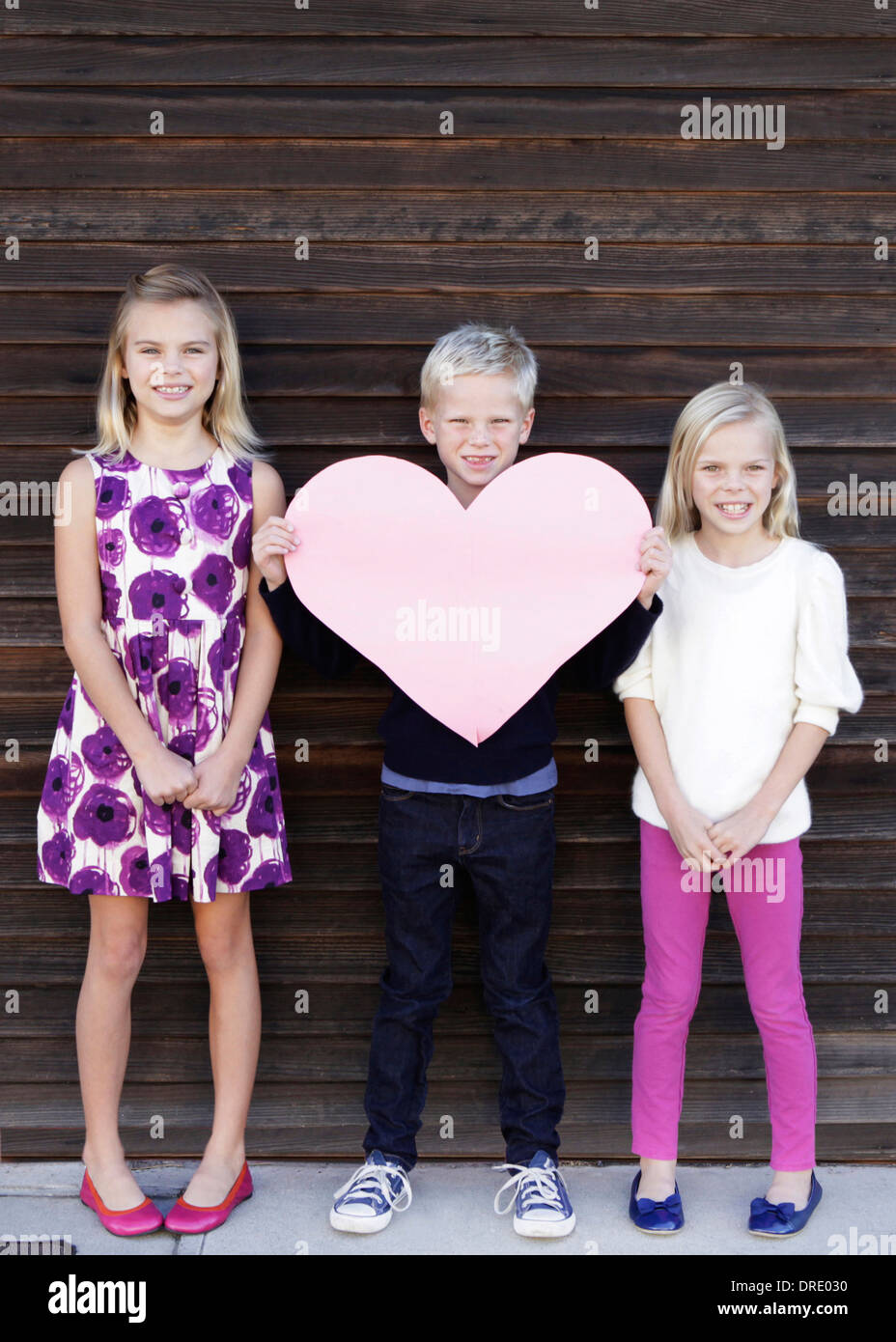Siblings holding up large paper heart Stock Photo