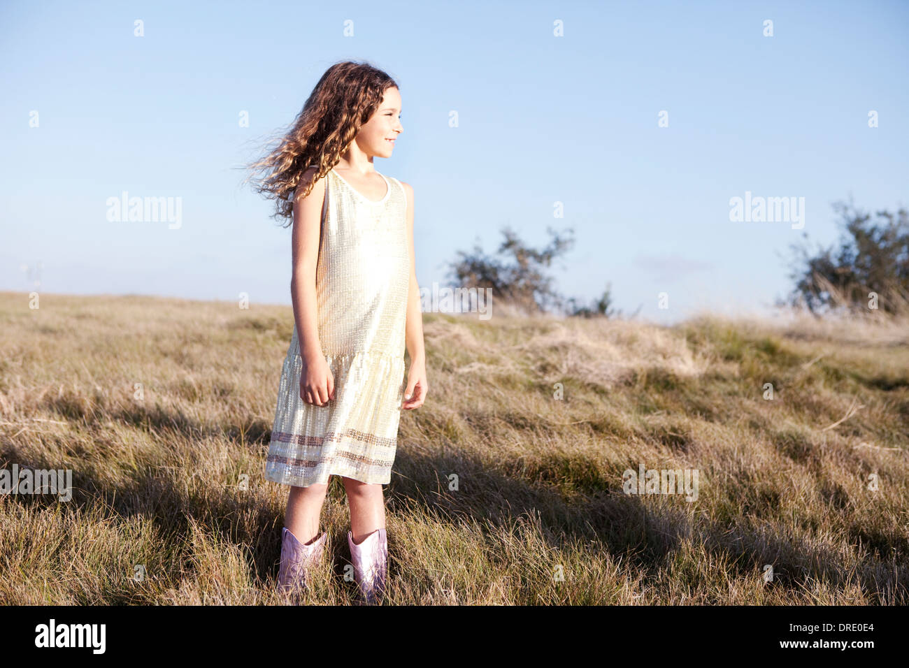 Young girl in dress on hillside - Stock Image