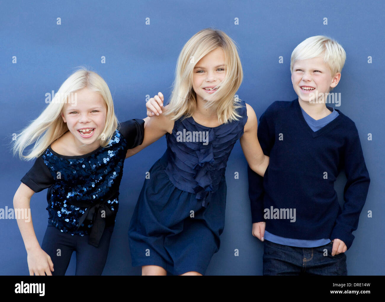 Portrait of siblings in front of blue background - Stock Image