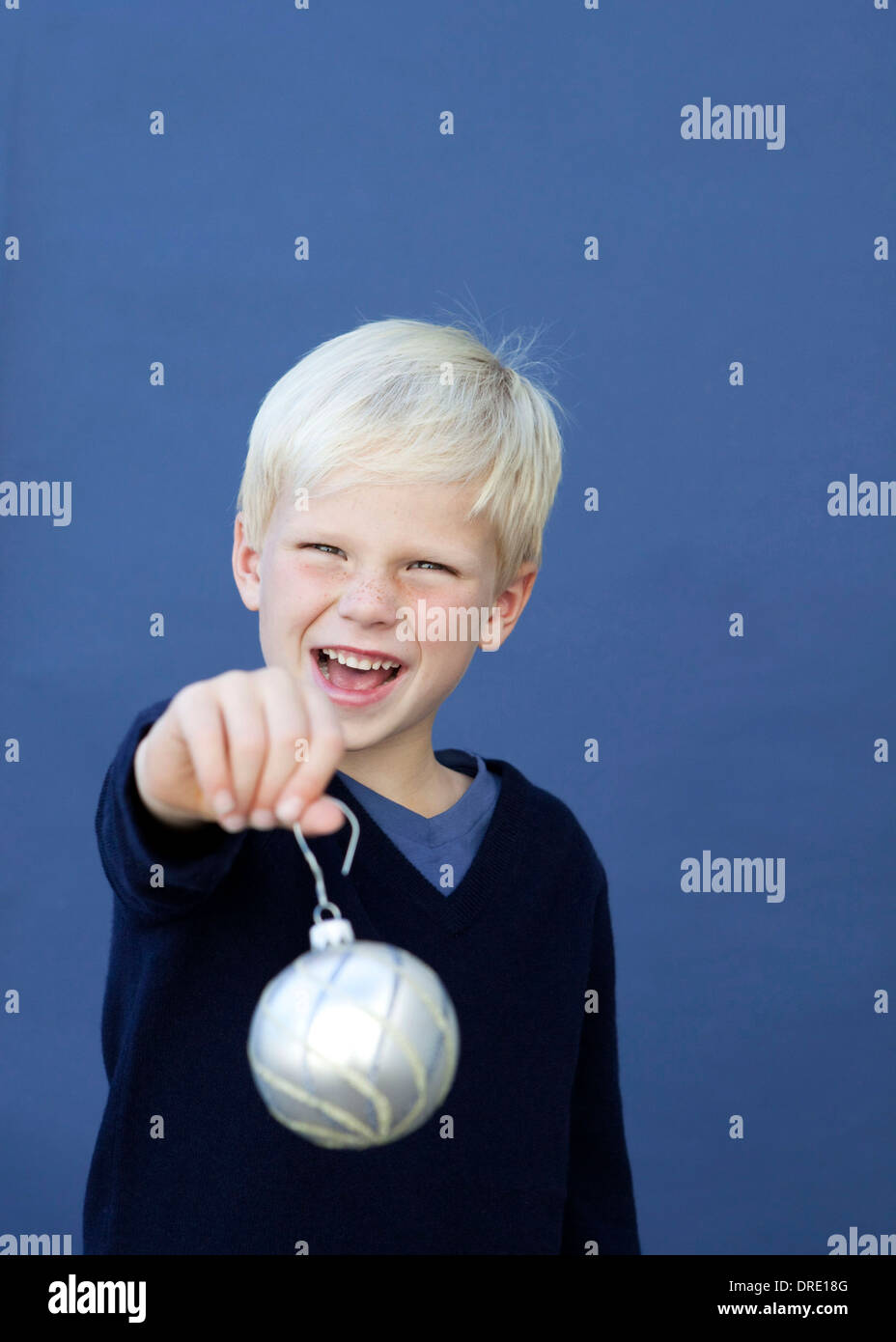 Portrait of young boy holding up ornament - Stock Image