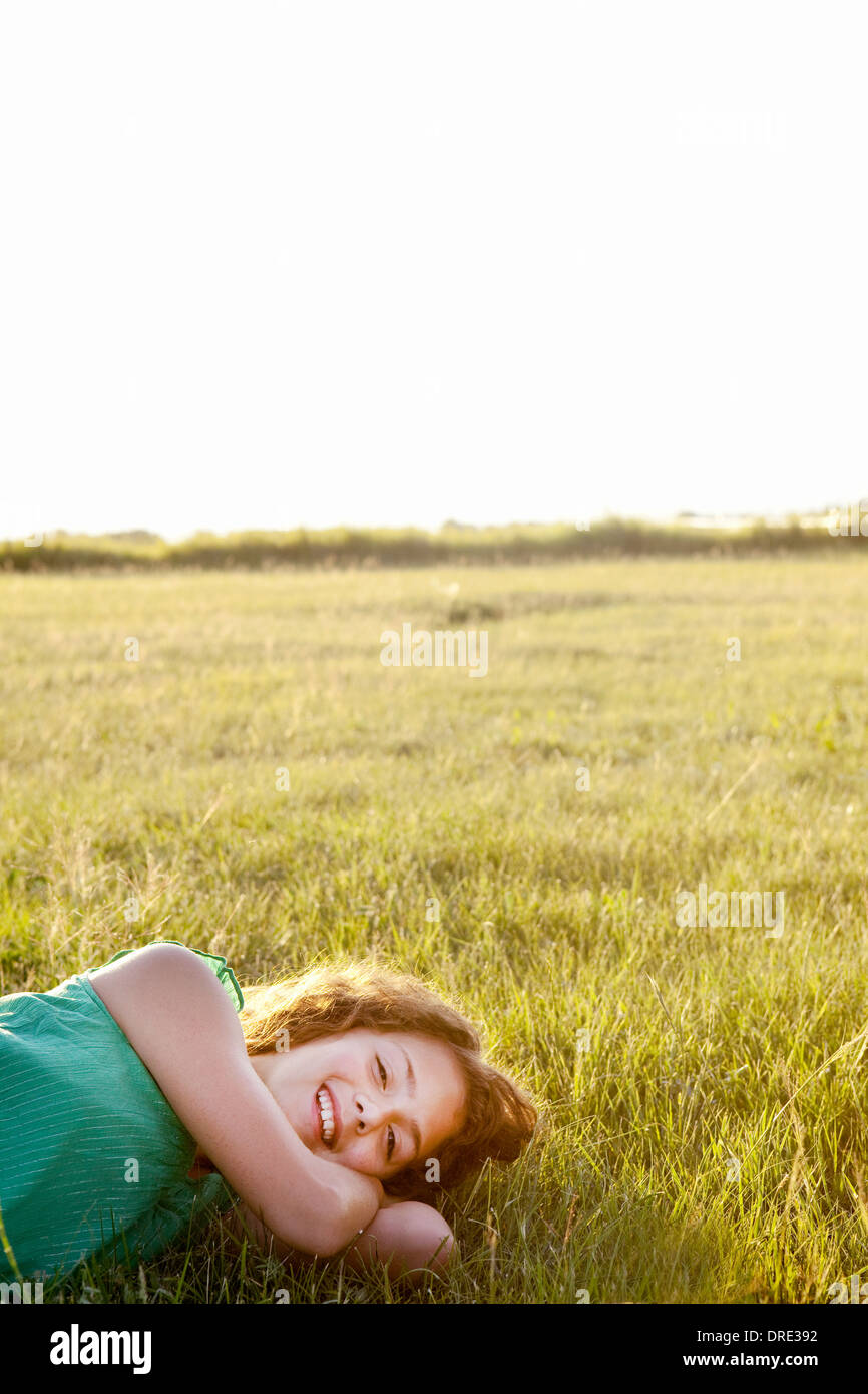 Young girl laughing as she lays in the field - Stock Image