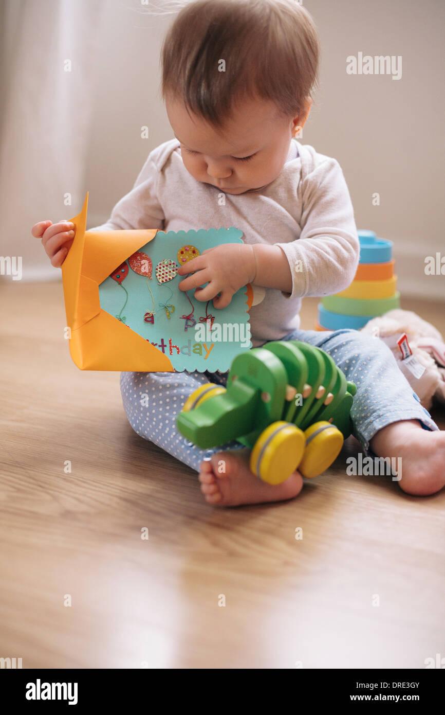 Baby opening birthday card - Stock Image