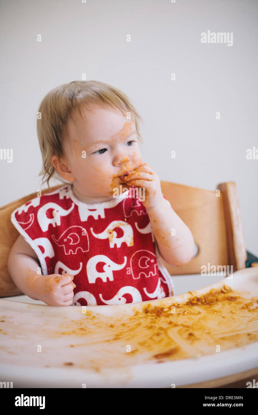 Young baby eating curry - Stock Image