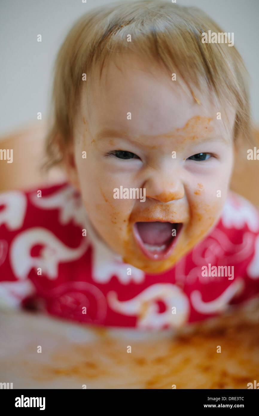 Baby covered in curry screaming - Stock Image
