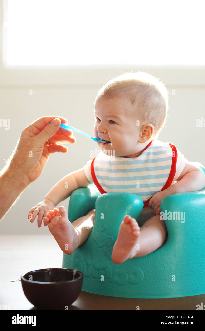 Baby being spoon fed - Stock Image