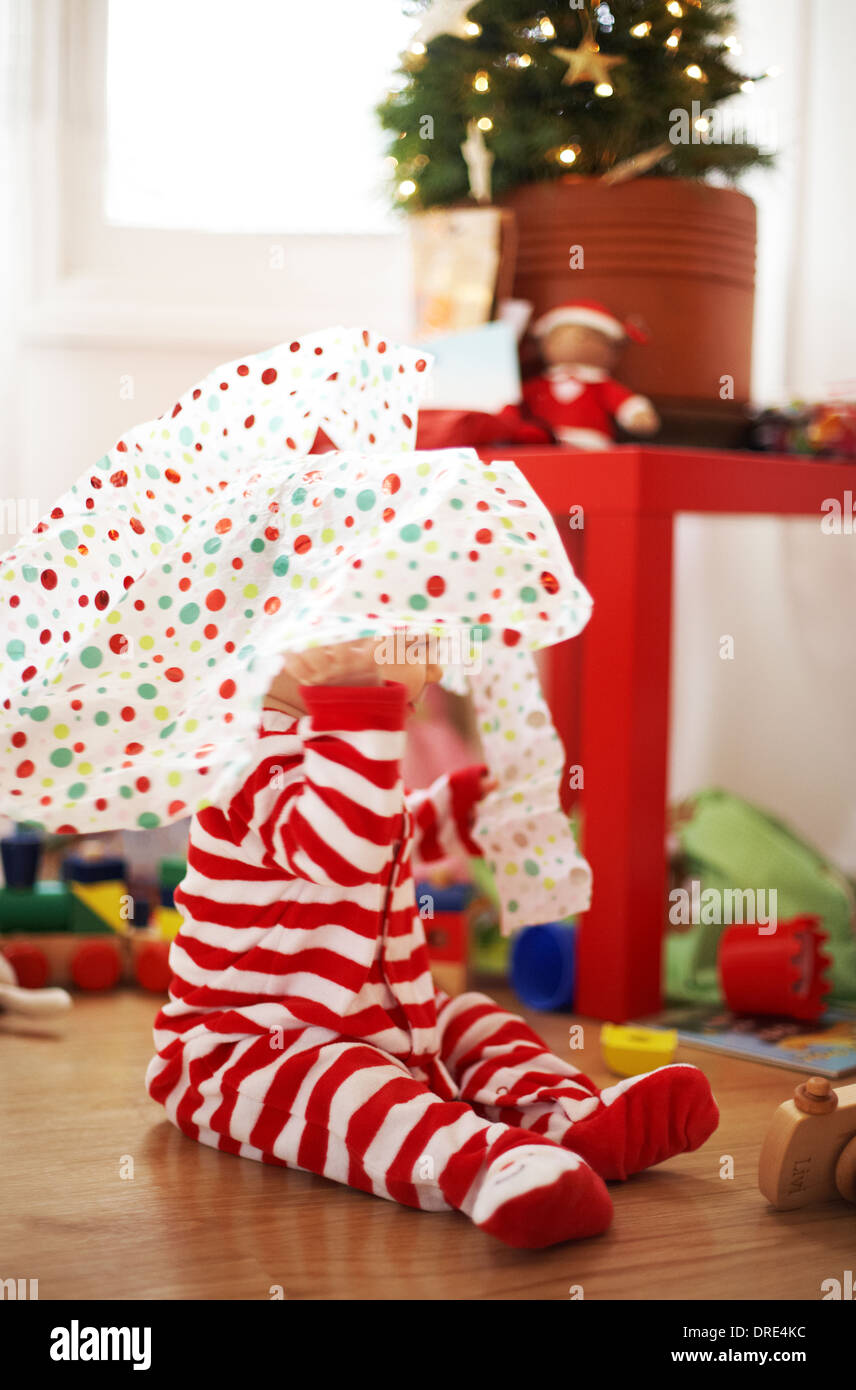 Baby opening christmas presents - Stock Image