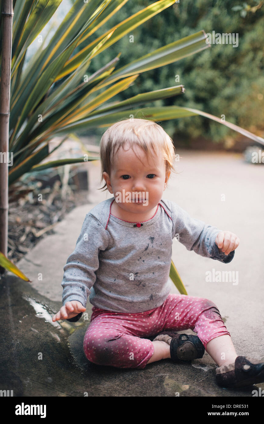 Baby girl sitting in landscaping - Stock Image
