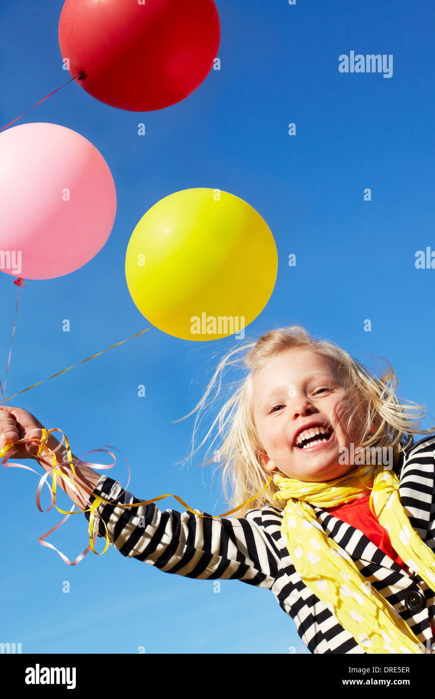 Girl with bunch of large balloons - Stock Image