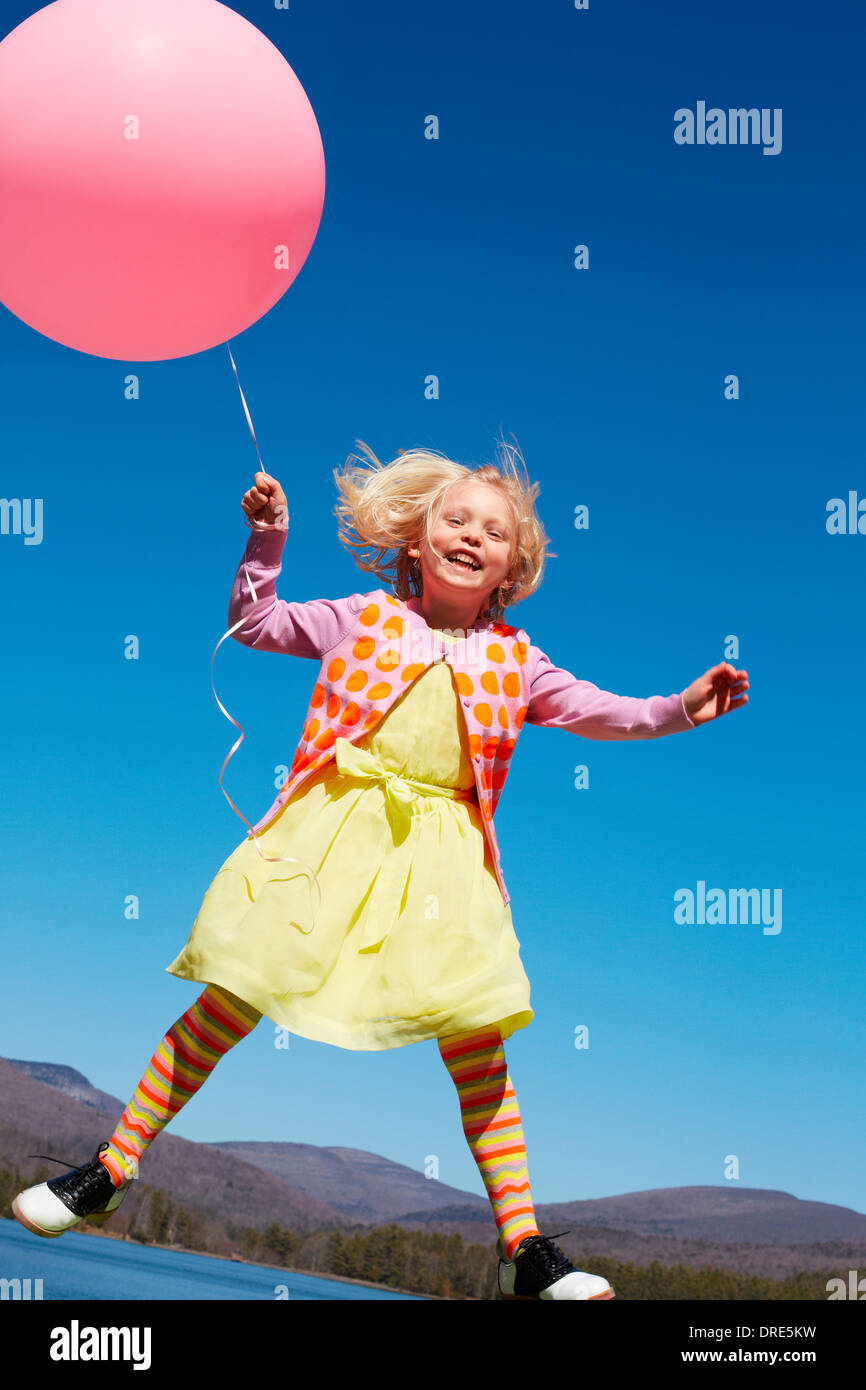 Girl outside with large red balloon - Stock Image