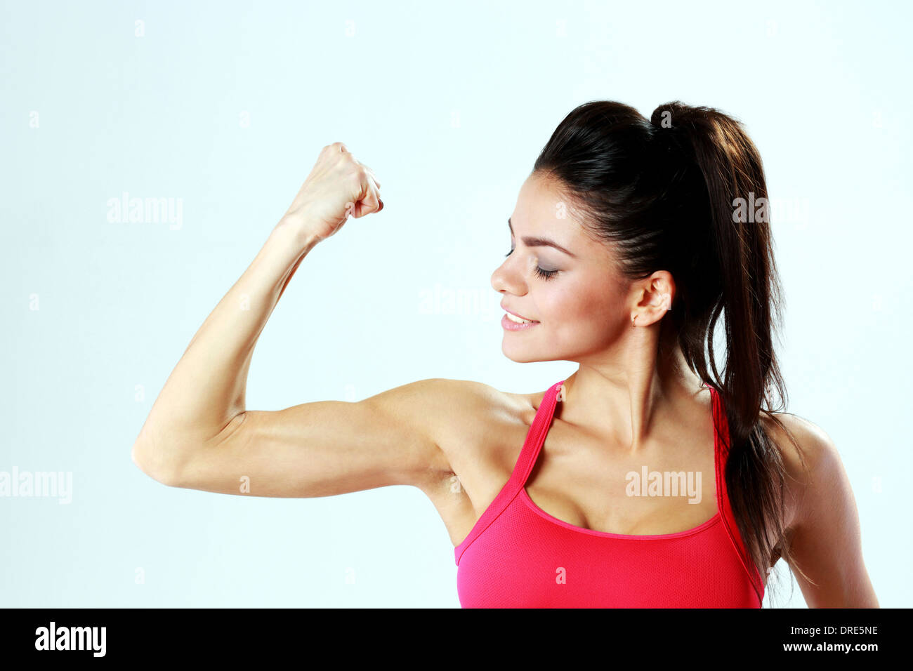 Young sport woman looking at her biceps on gray bakground - Stock Image