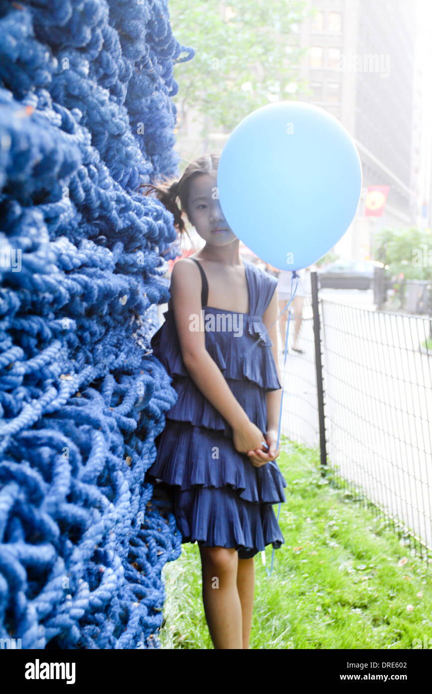 Young asian girl in blue dress with balloon - Stock Image