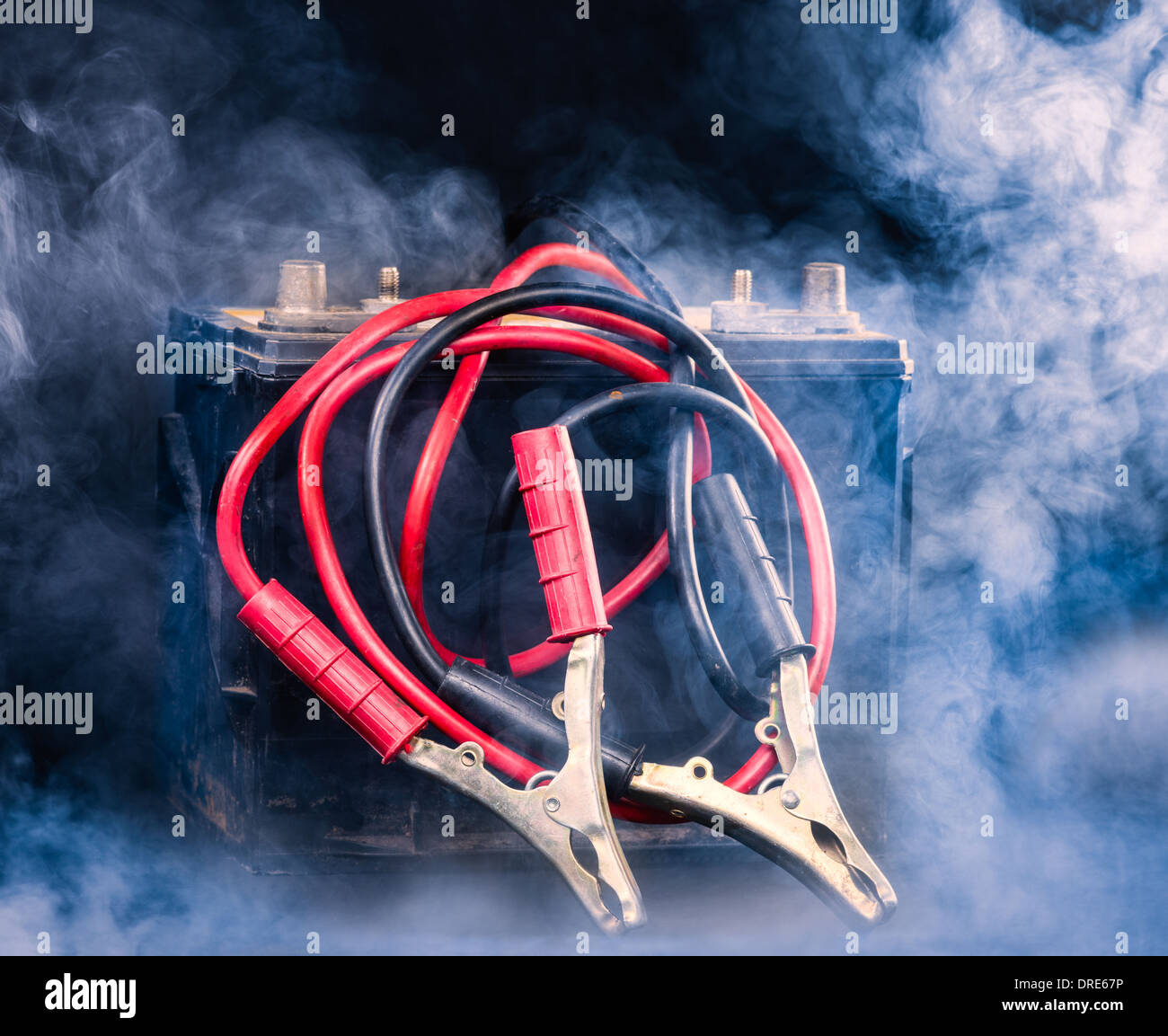 Old car battery and the jumper cables, smoky environment - Stock Image