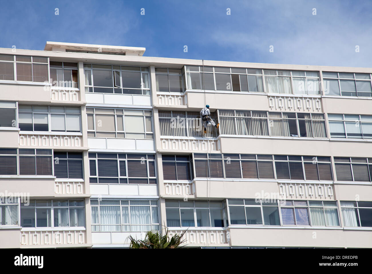 Window Cleaner Abseiling on Apartment exterior in sea Point - Cape Town - South Africa Stock Photo