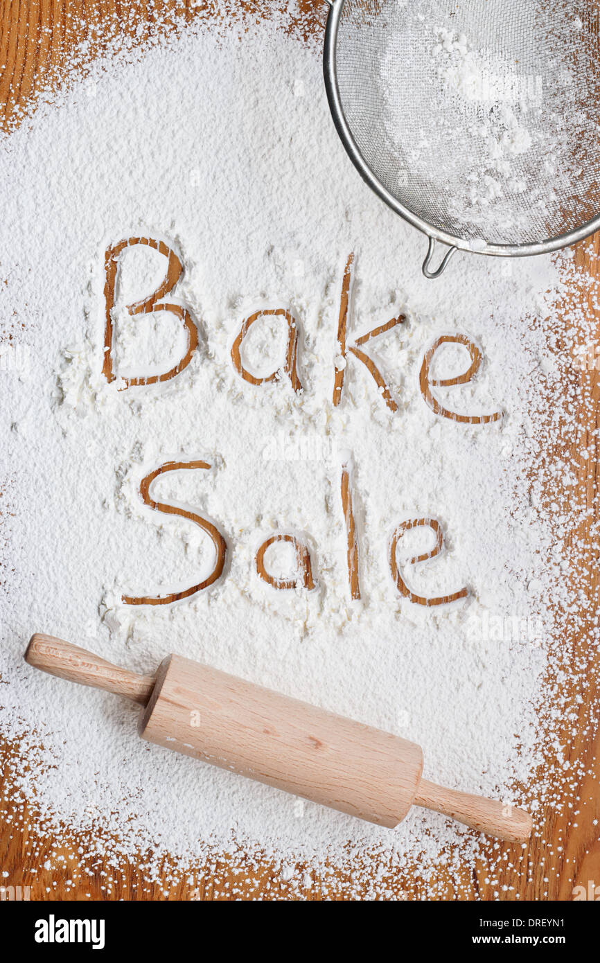 Flour on a wooden table symbolising a Bake Sale Notice - Stock Image
