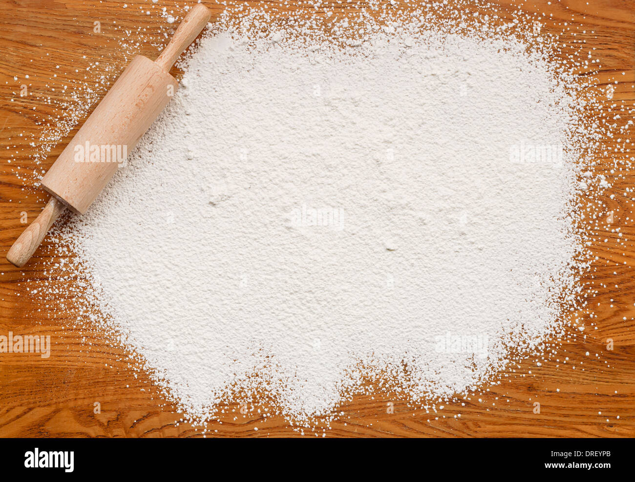 White flour on a wooden table creating a text area for insertion of your custom message or recipe - Stock Image