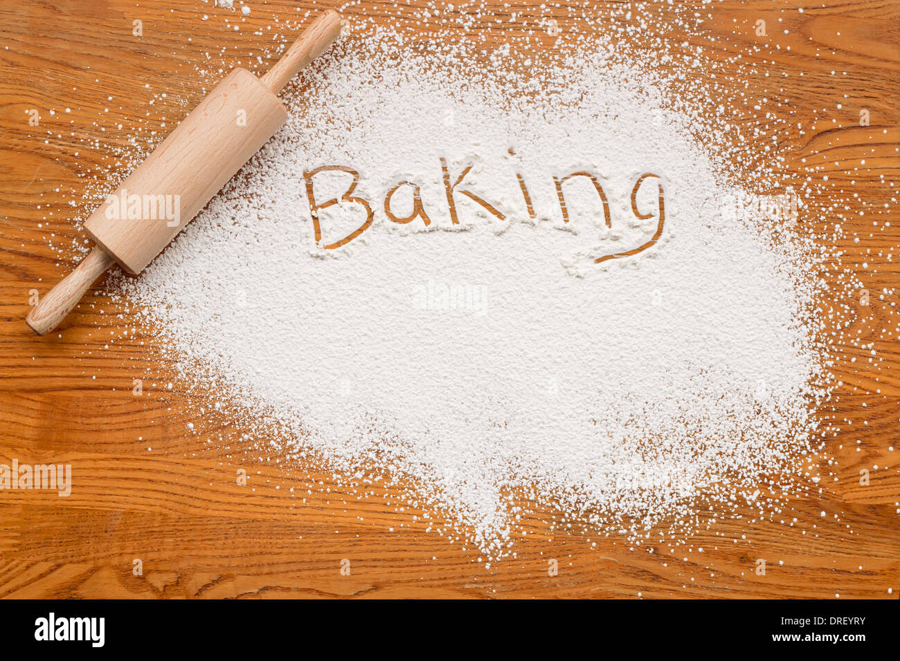 Flour on a wooden table symbolising a Bakery Baking Notice with white space for inclusion of text. - Stock Image