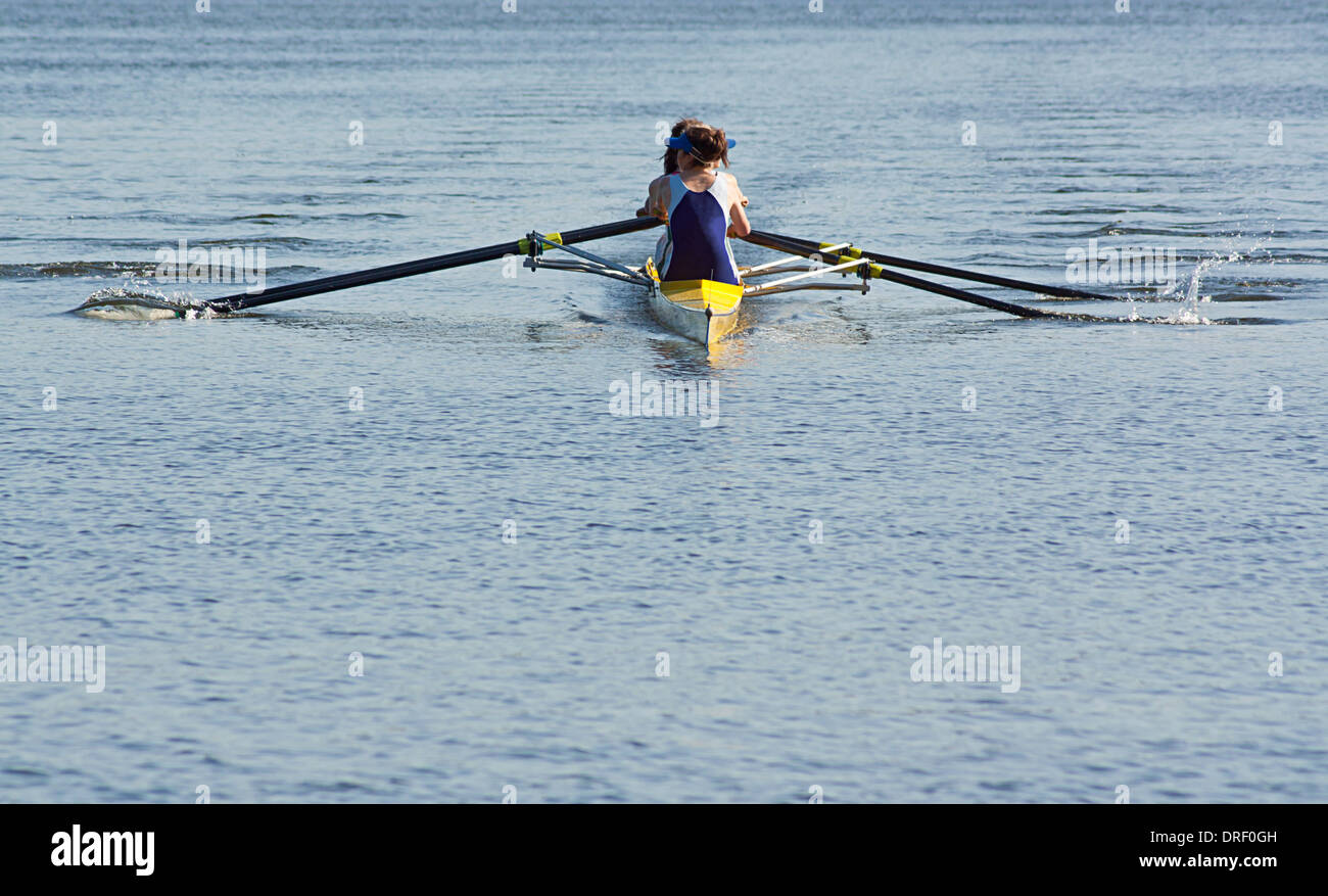 Rowing team working in unison to compete in a regatta by racing specially built row boats - Stock Image