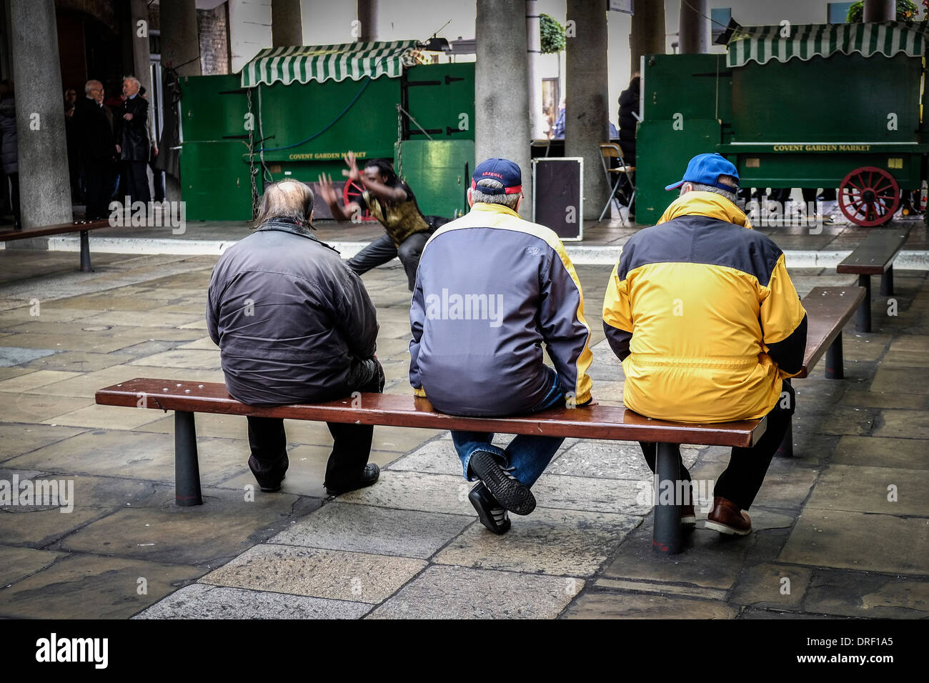 Three men watching a street entertainer in the North Hall in Covent Garden. - Stock Image
