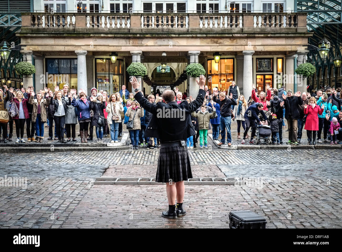 Pete Dobbing a street entertainer at Covent Garden Piazza encourages the audience to participate in his performance. - Stock Image
