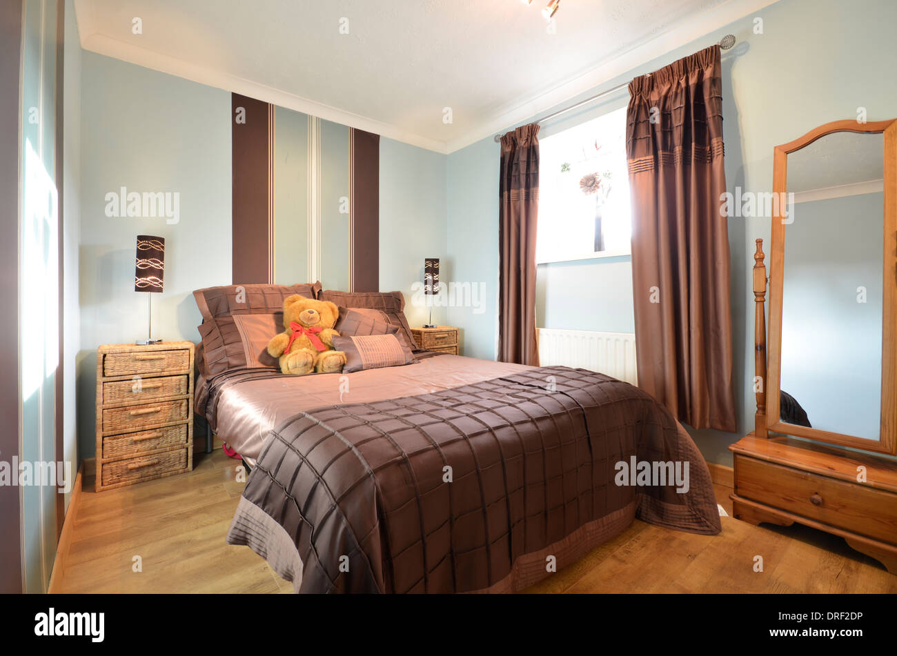 stylish spare bedroom with double bed and pine furniture - Stock Image