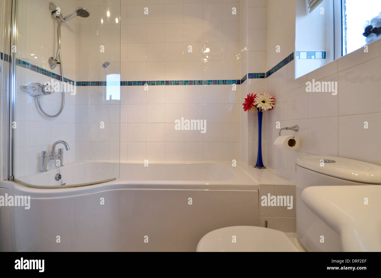 Curved Shower Screens Over Bath small bathroom with bath and curved shower screen stock photo