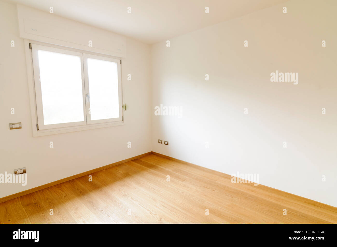 Spacious empty room with white walls, window and parquet floor - Stock Image