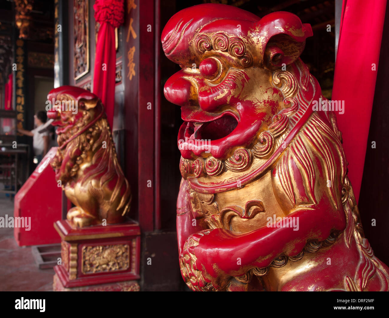 Two grotesque red and gold figures stand guard beside the door of a Chinese temple in Malaysia. - Stock Image