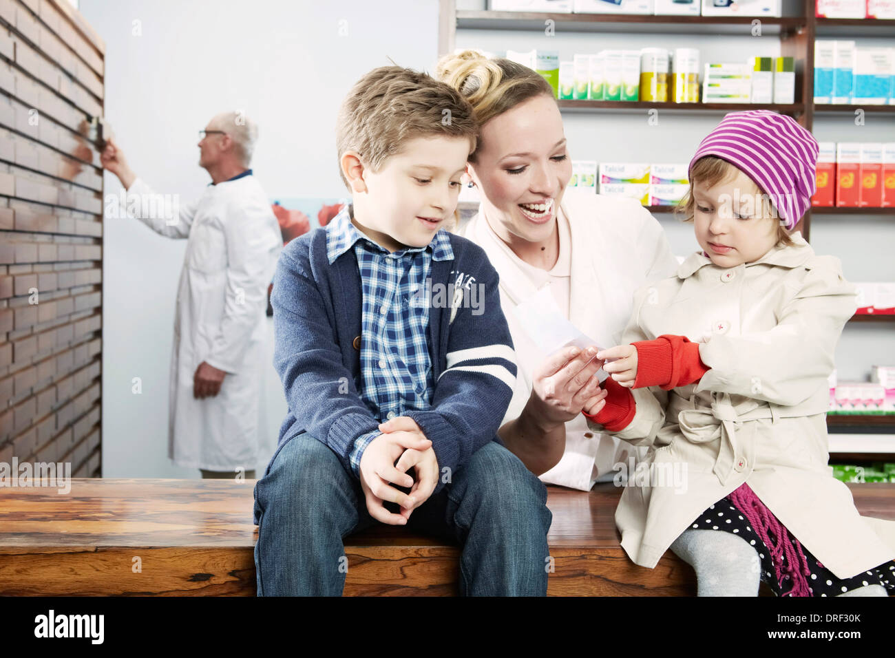 Female Pharmacist Talking With Children, Munich, Bavaria, Germany - Stock Image