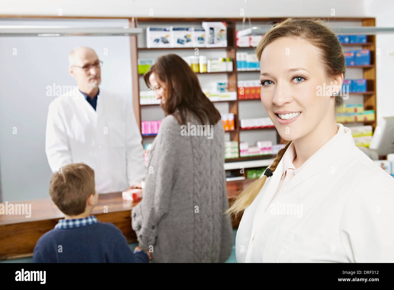 Portrait Of A Female Pharmacist, Customers in Background, Munich, Bavaria, Germany - Stock Image