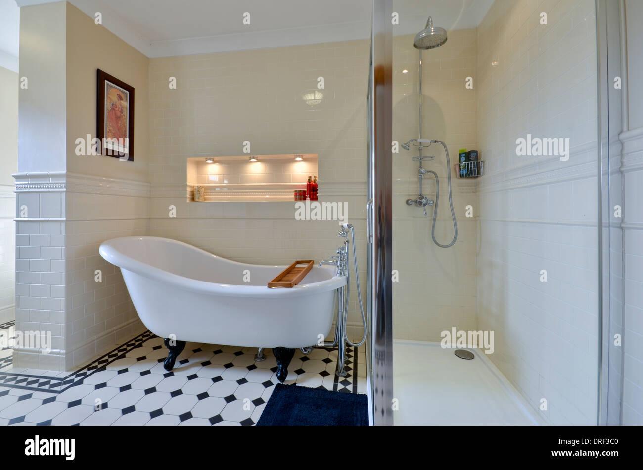 Roll top bath and shower in cream bathroom Stock Photo: 66100160 - Alamy