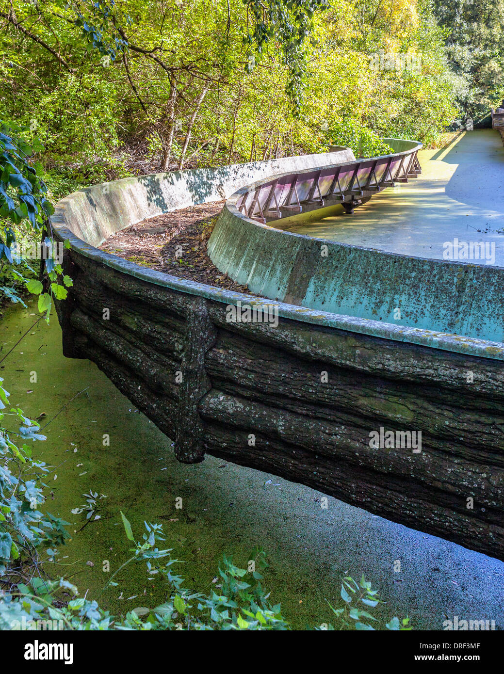 Rusty, dirty, grimy canal of fun water ride over murky, slimy pond at disused amusement park - Spreepark, Planterwald, Berlin - Stock Image