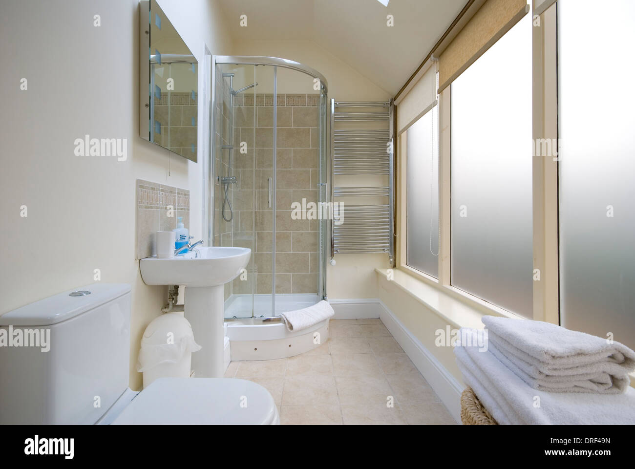 Long thin shower room with large opaque windows - Stock Image