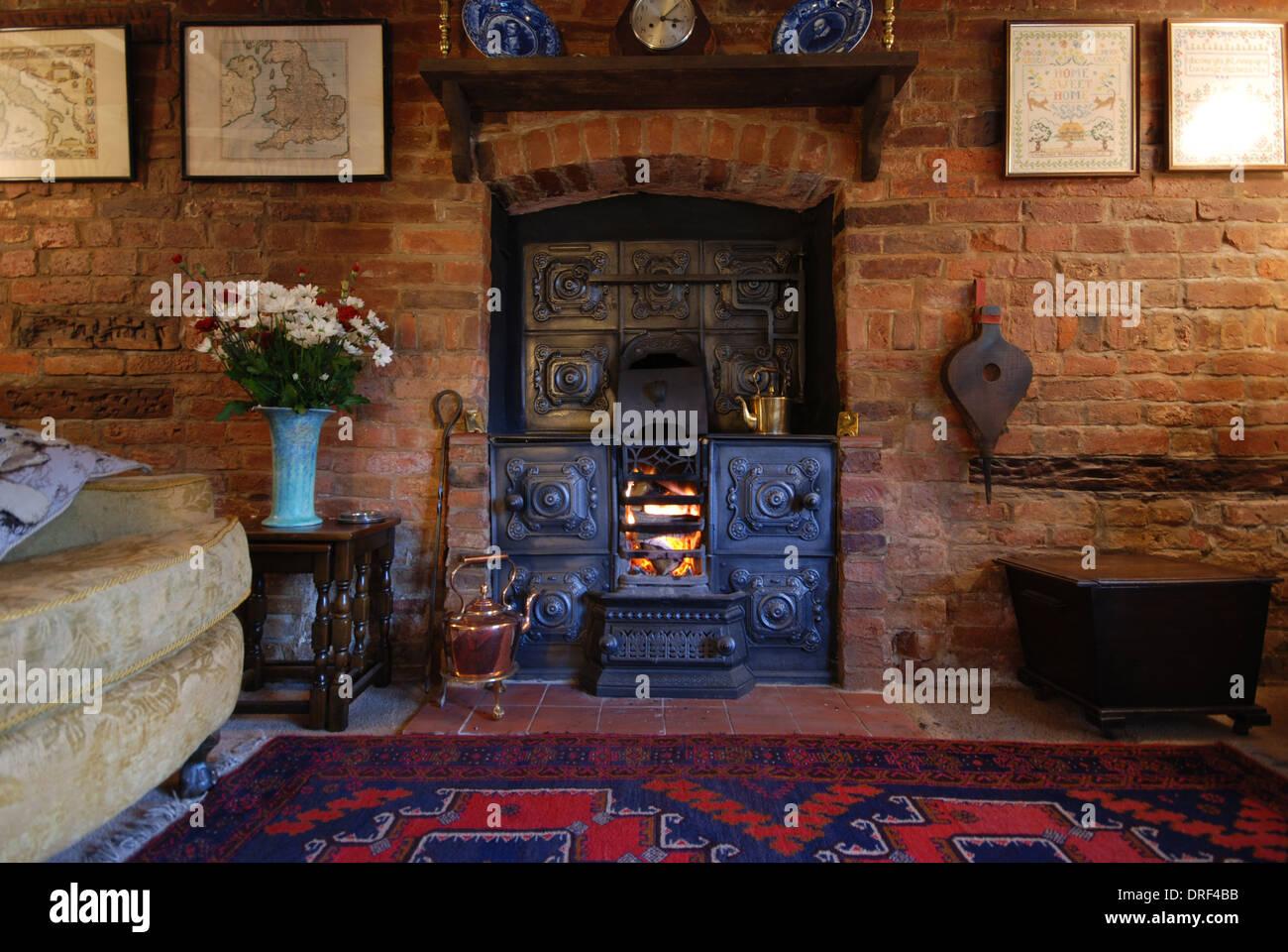 Old cottage cast iron stove fireplace - Stock Image