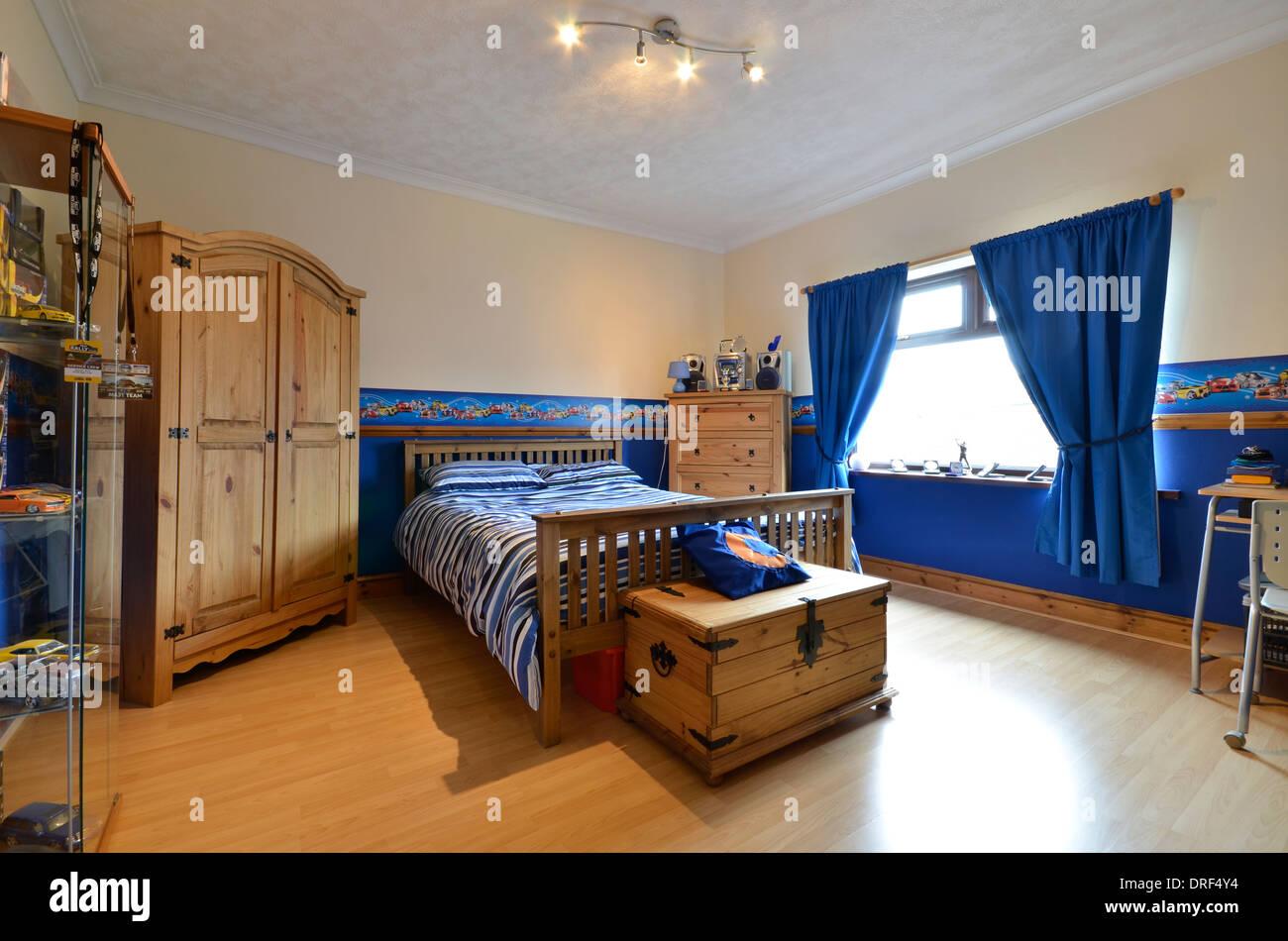 Teenage boy bedroom in blue with pine wardrobe - Stock Image