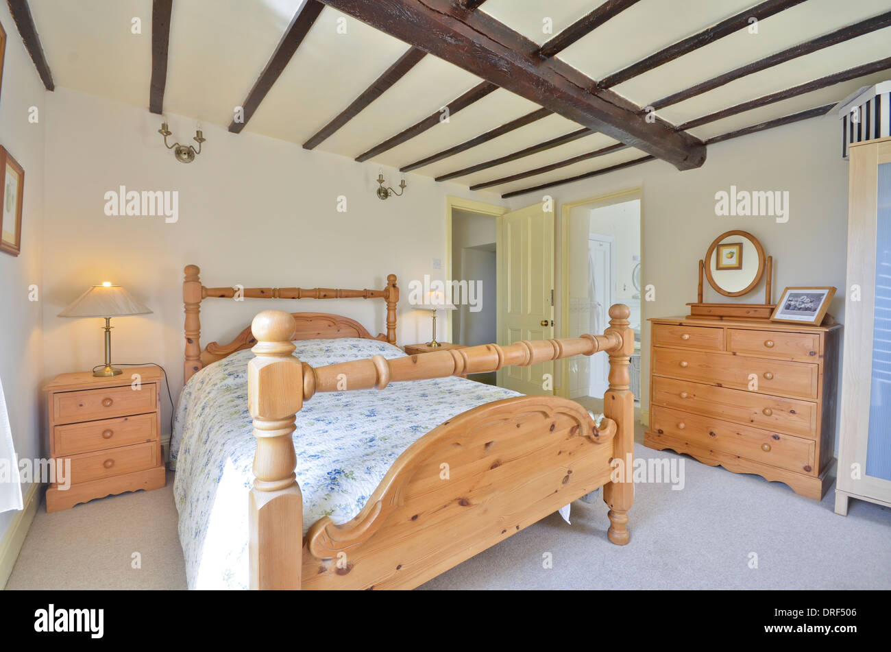 Spare bedroom with pine framed double bed and pine furniture Stock Photo