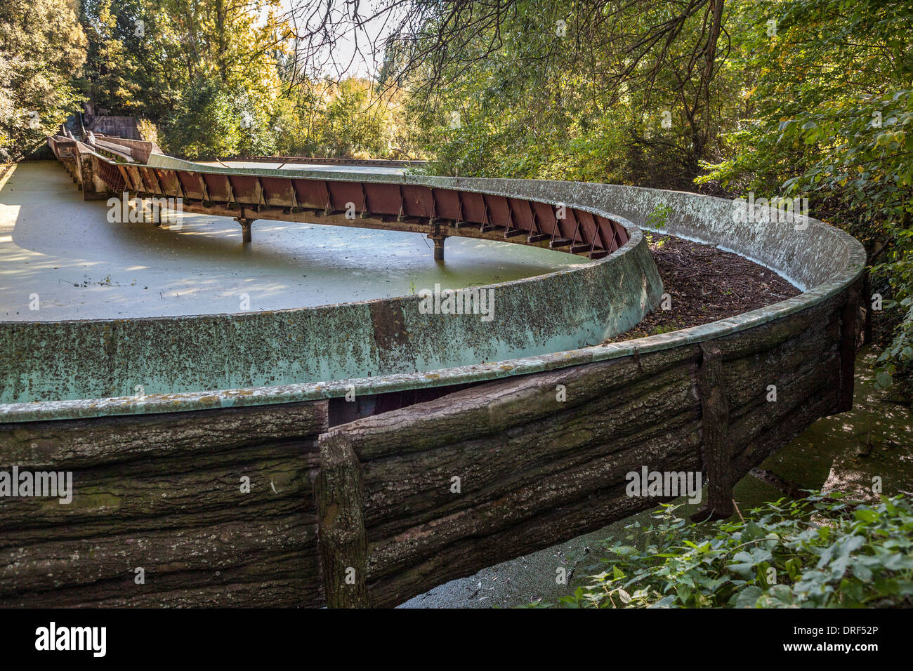 Empty, dirty canal of fun ride over dirty, murky pond at, derelict, disused amusement park - Spreepark, Planterwald, Berlin - Stock Image