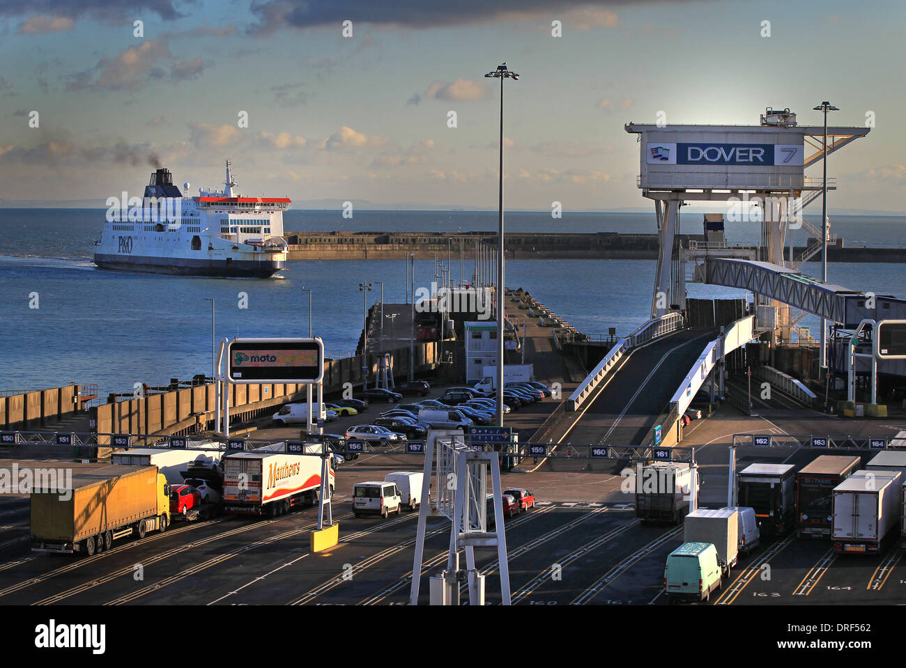 A ferry comes into port on a sunny day as lorries queue to embark at the Eastern Docks - Stock Image