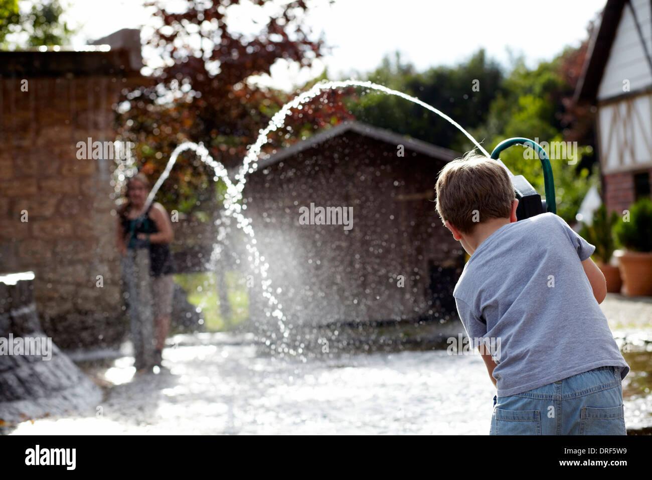 Two Boys Playing With Water, Bad Woerrishofen, Bavaria, Germany, Europe - Stock Image