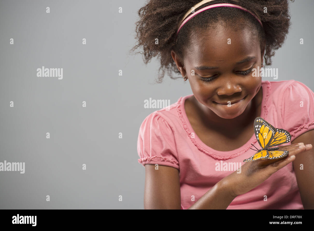 Utah USA girl with yellow butterfly on her hand motionless - Stock Image