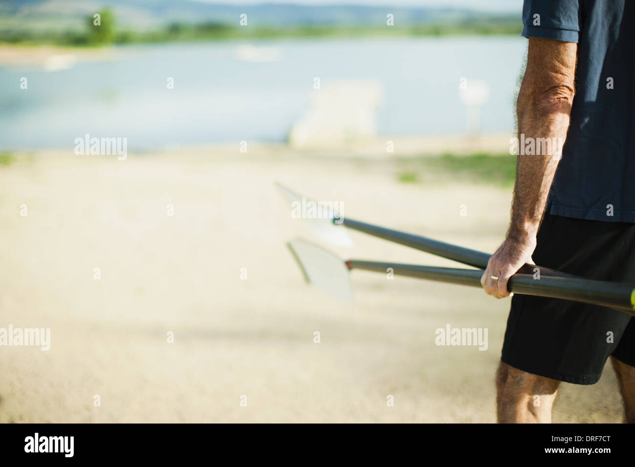 Colorado USA middle-aged man carrying oars pontoon river - Stock Image