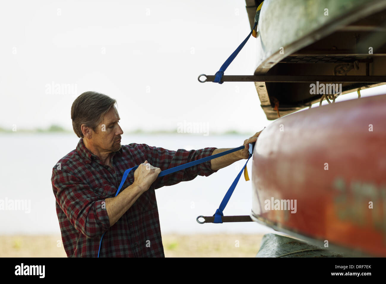 Colorado USA man stacking rowing boats lashing onto trailer - Stock Image