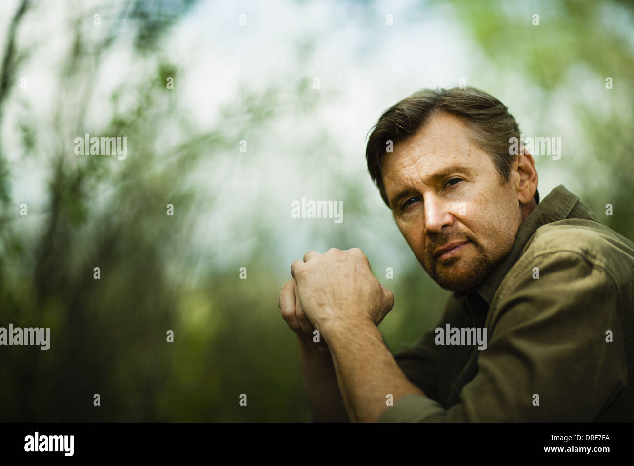 Colorado USA middle-aged man sits looking pensive hands folded - Stock Image