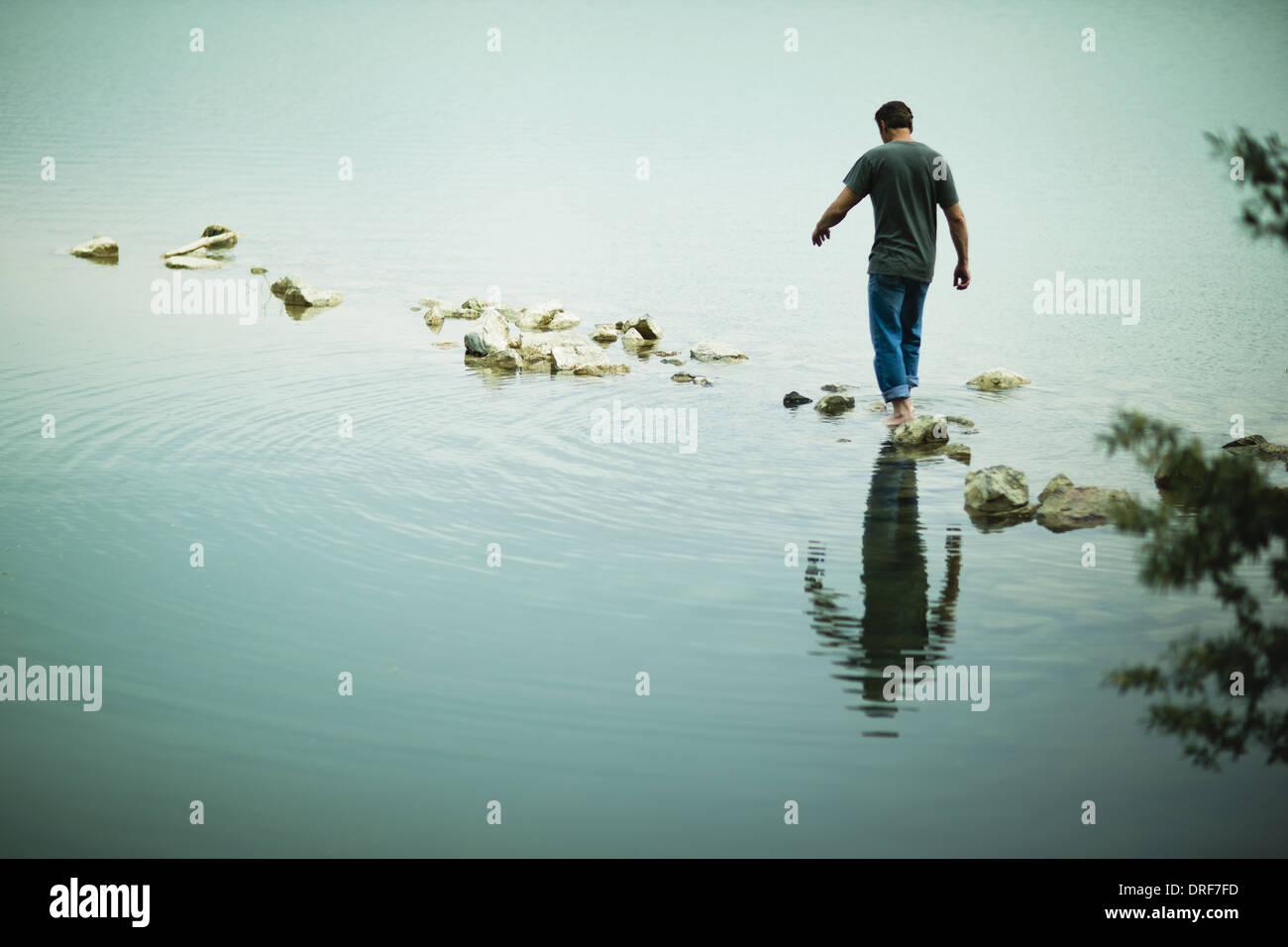 Colorado USA man walking barefoot across stepping stones lake - Stock Image