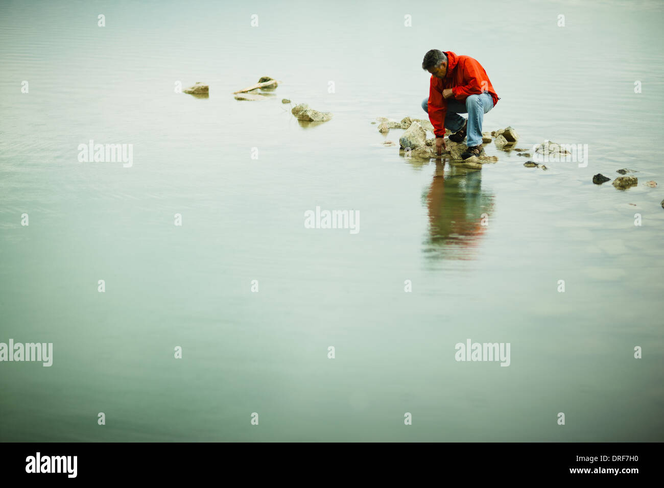 Colorado USA man balanced on stepping stone pensive pose - Stock Image