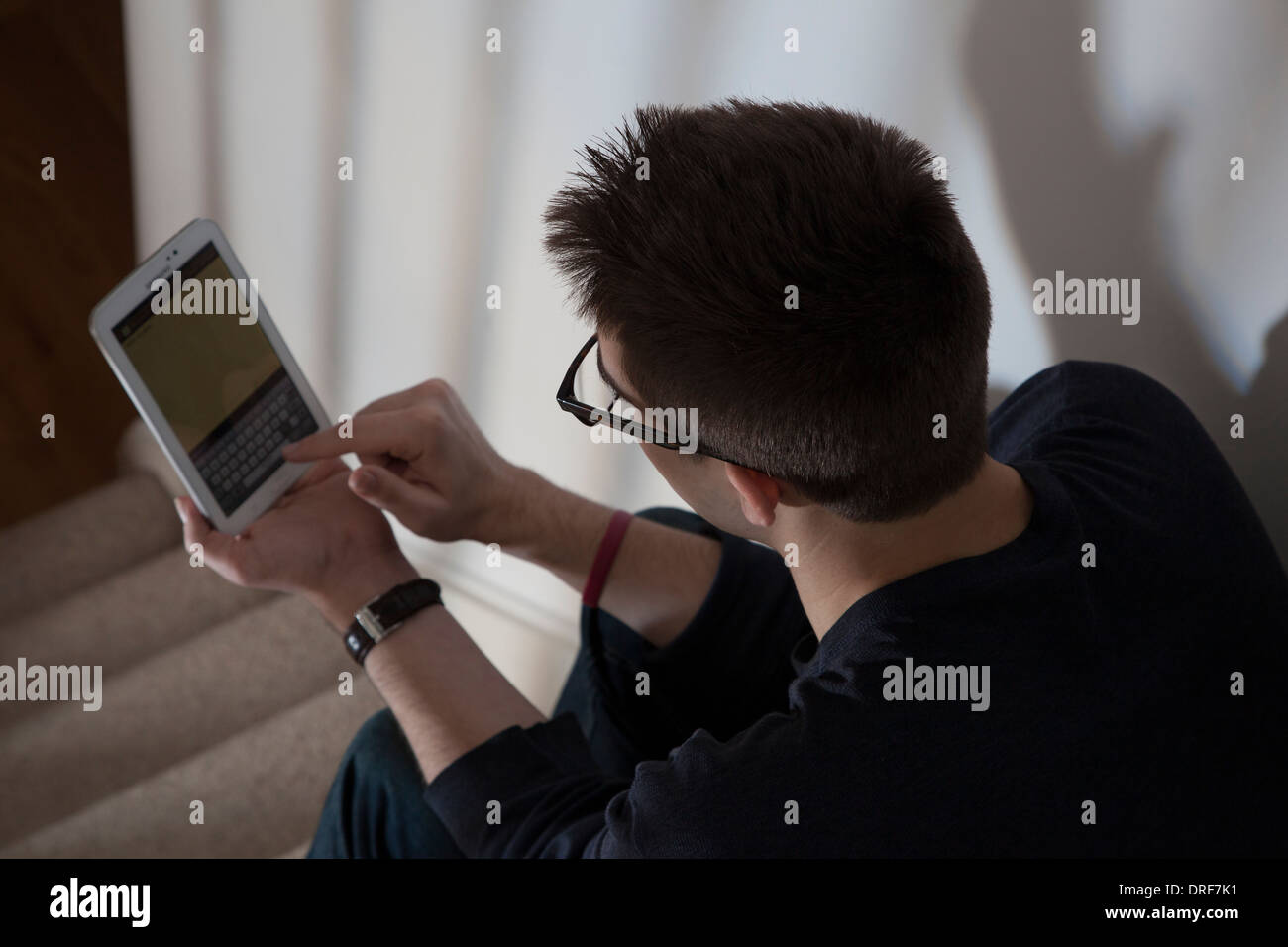 Over shoulder shot of man wearing glasses typing on a keypad on the touch screen digital tablet. - Stock Image