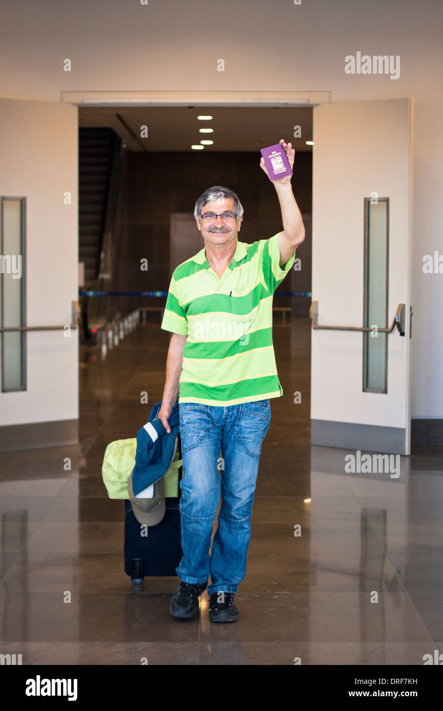 Happy senior tourist man waving with passport in airport arrival hall. - Stock Image